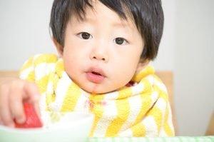 Kind isst Erdbeere und hat Fleck auf Kleidung