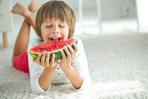 Kind liegt auf hellem Teppich und beißt in eine Melone
