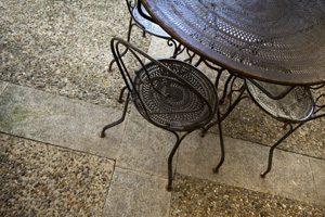 Terassenmöbel aus Metall stehen auf steinernem Untergrund