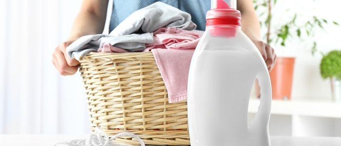 weißes Waschmitte in neutraler Flasche vor einem Wäschekorb