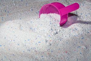 rosafarbener Messlöffel liegt in Waschpulver