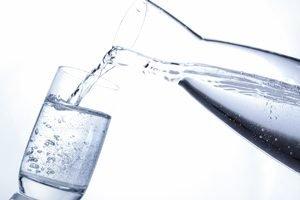 Wasser wird aus einer Karaffe in ein Glas gegossen