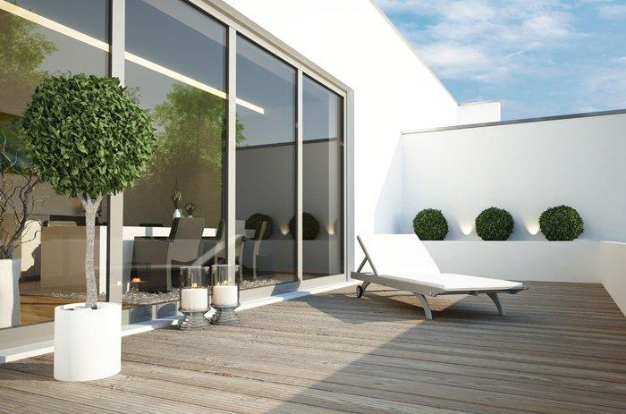 weitläufiger Balkon mit Dielen und weißer Liege