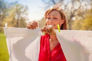 Frau hängt Wäsche auf