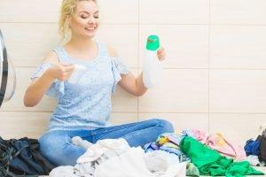 frau kann sich nicht entscheiden zwischen flüssigwaschmittel oder pulver gegen flecken