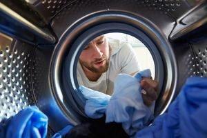 Mann beim Wäsche färben in der Waschmaschine