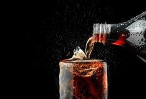 Cola wird aus Flasche in Glas gegossen
