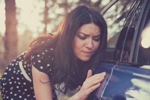besorgte Frau inspiziert den Lack ihres Autos