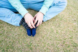 Person kratzt sich an Fuß mit Socke