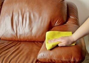 Hand wischt mit gelbem Lappen Ledersofa ab