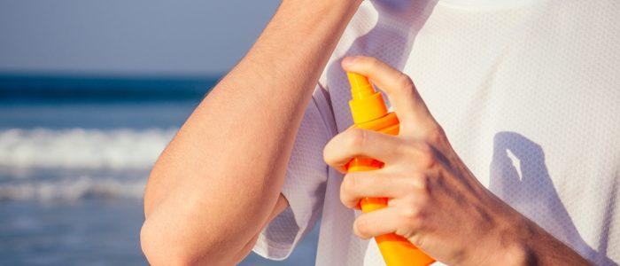 Oberkörper eines Mannes im Shirt mit Sonnencreme vor dem Meer