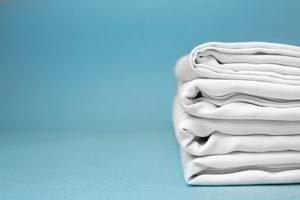 ein Stapel Betttücher auf blauem Grund