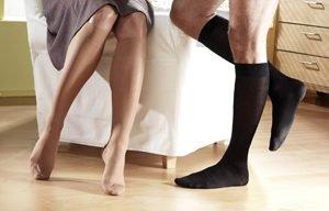 Männer- und Frauenbeine in verschiedenen Strümpfen