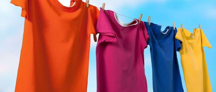 bunte Shirts hängen auf einer Leine vor blauem Himmel