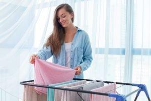 Frau hängt Wäschestücke auf Wäscheständer