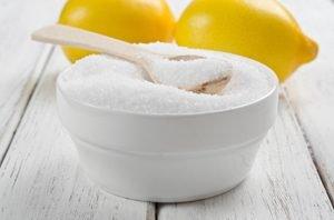Zitronensäure in Pulverform und Zitronen