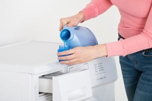 Frau gießt flüssiges Waschmittel auf Waschmaschine in Becher