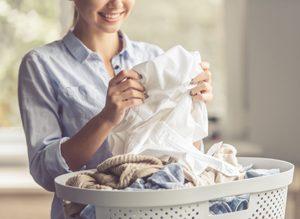 junge Frau freut sich über saubere Wäsche