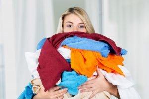 frau haelt waesche fuer die waschmaschine