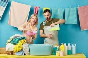 Paar mit Waesche und verschiedenen Waschmitteln
