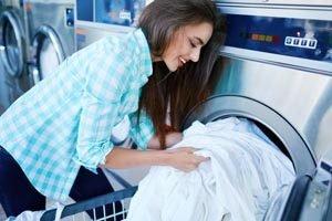 Frau mit weißem Leinen vor Waschmaschine