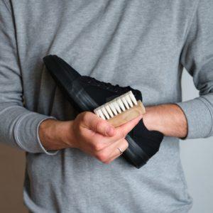 mann mit schwarzen sneakern und bürste