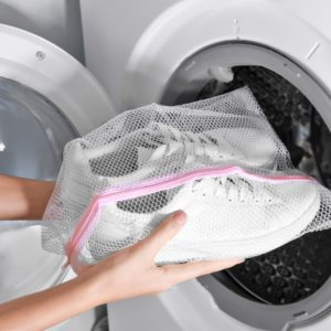 frau legt sneaker in die waschtrommel